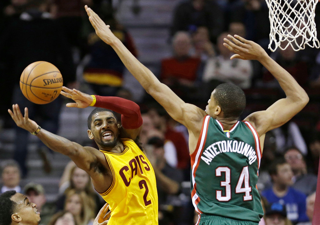. Milwaukee Bucks\' Giannis Antetokounmpo (34), from Greece, puts pressure on Cleveland Cavaliers\' Kyrie Irving (2) during an NBA basketball game Wednesday, Dec. 31, 2014, in Cleveland. (AP Photo/Tony Dejak)
