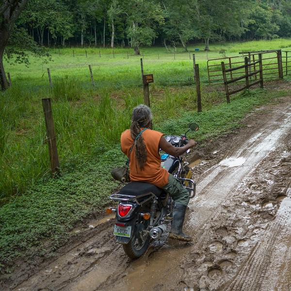 Motorcyclist on wet dirt road, Chaa Creek Road, Chaa Creek Nature Reserve, San Ignacio, Belize