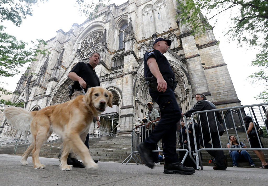 . Officials walk with a dog as they secure an area outside of at Cathedral Church of Saint John the Divine, where people gathered behind a barricade, before funeral services for actor James Gandolfini, Thursday, June 27, 2013, in New York. (AP Photo/Julio Cortez)