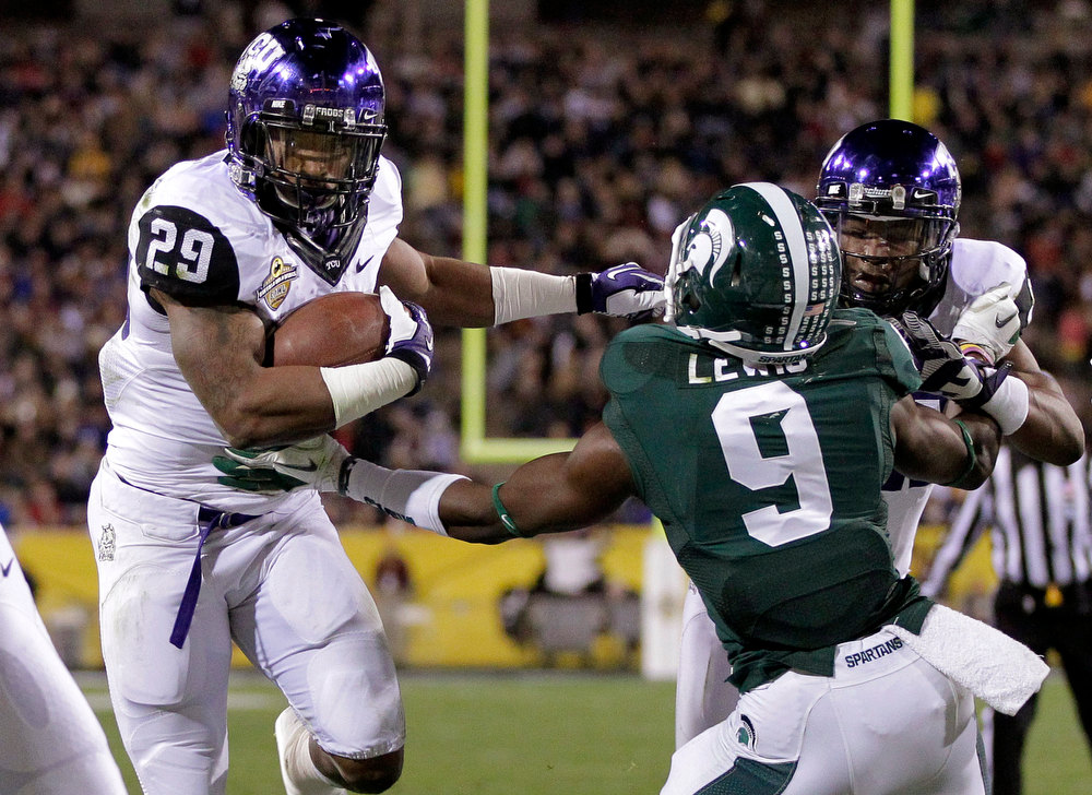 Description of . TCU running back Matthew Tucker (29) breaks the tackle of Michigan State safety Isaiah Lewis (9) for a touchdown during the first half of the Buffalo Wild Wings Bowl NCAA college football game, Saturday, Dec. 29, 2012, in Tempe, Ariz. (AP Photo/Matt York)