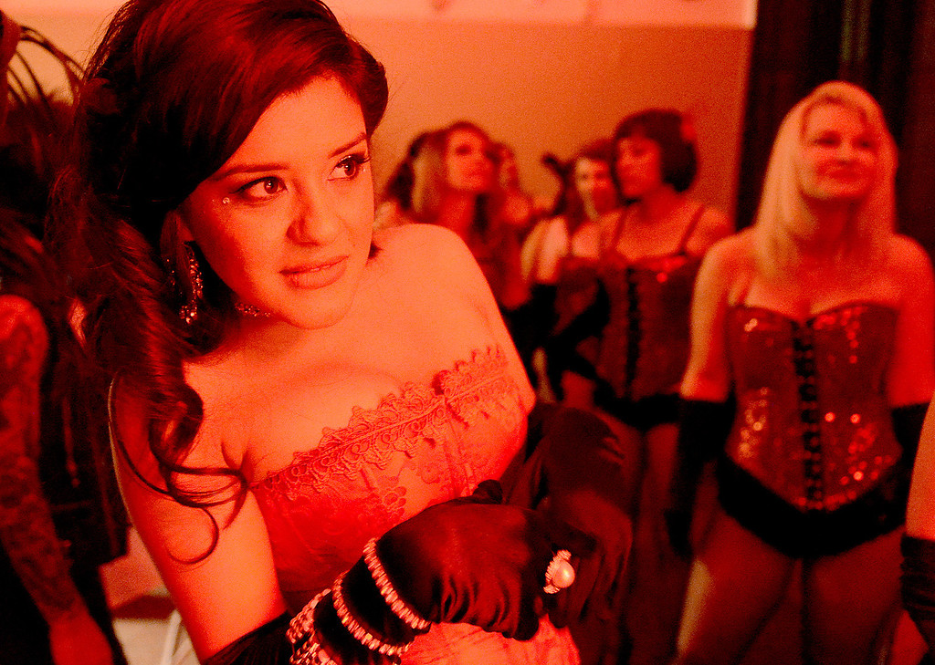 . Red lights from the stage are seen on Natalie Rudyko as she peeks from backstage before her first burlesque performance at Cal State San Bernardino May 18, 2013.  (Staff photo by Thomas Cordova)