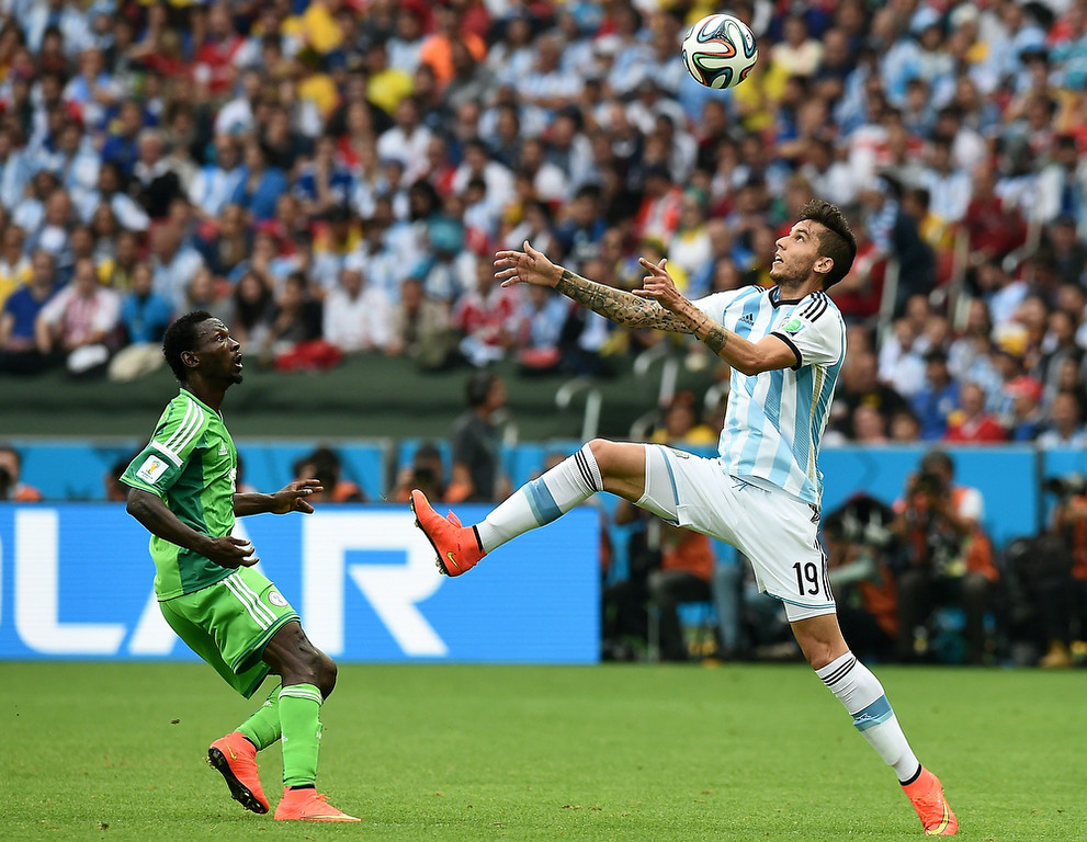 . Nigeria\'s midfielder John Obi Mikel (L) looks on as Argentina\'s midfielder Ricky Alvarez rises to head the ball during the Group F football match between Nigeria and Argentina at the Beira-Rio Stadium in Porto Alegre on June 25, 2014,during the 2014 FIFA World Cup. (JEWEL SAMAD/AFP/Getty Images)