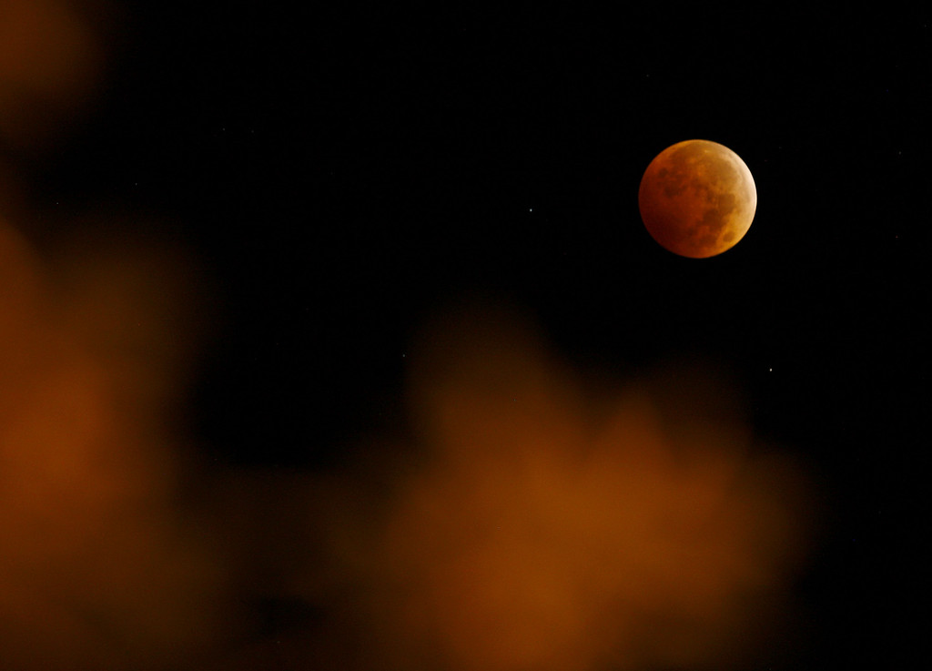 . A lunar eclipse appears above City Park in Casper, Wyo. in the early hours of Wednesday, Oct. 8, 2014. The moon appears orange or red, the result of sunlight scattering off Earth\'s atmosphere. This is known as the blood moon.  (AP Photo/The Casper Star-Tribune, Dan Cepeda)