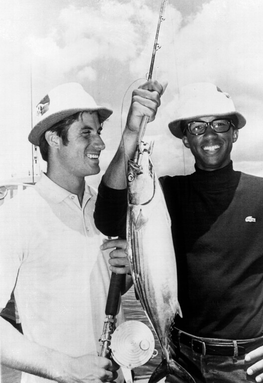 . Arthur Ashe, right, and Charles Pasarell, members of the U.S. Davis Cup Tennis team, show off the fish they caught off Maroubra Beach near Sydney, Australia, with the Brighton-Le-Sands amateur fishermen\'s club, Jan. 2, 1969.  (AP Photo)