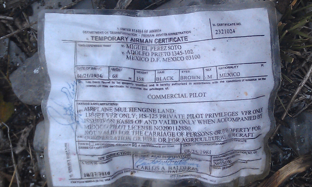 . A temporary airman\'s certificate issued by the Federal Aviation Administration (FAA) sits on the ground at the crash site where a plane carrying U.S. born singer Jenni Rivera apparently crashed near Iturbide, Mexico Sunday Dec. 12, 2012. The wreckage of a small plane believed to be carrying Rivera, the singer whose soulful voice and unfettered discussion of a series of personal travails made her a Mexican-American superstar, was found in northern Mexico on Sunday. Authorities said there were no survivors. (AP Photo)