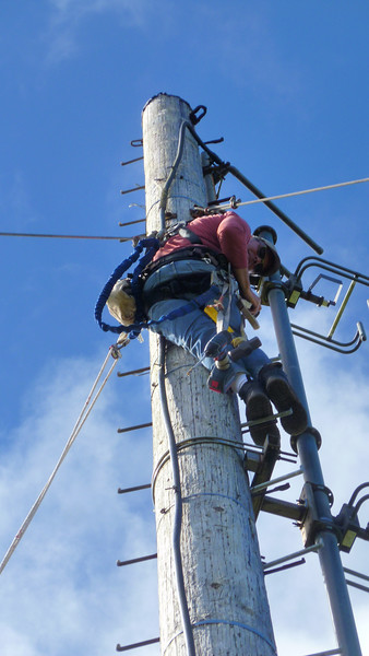 Joe Bakos adding new climbing pegs at 50 feet above ground