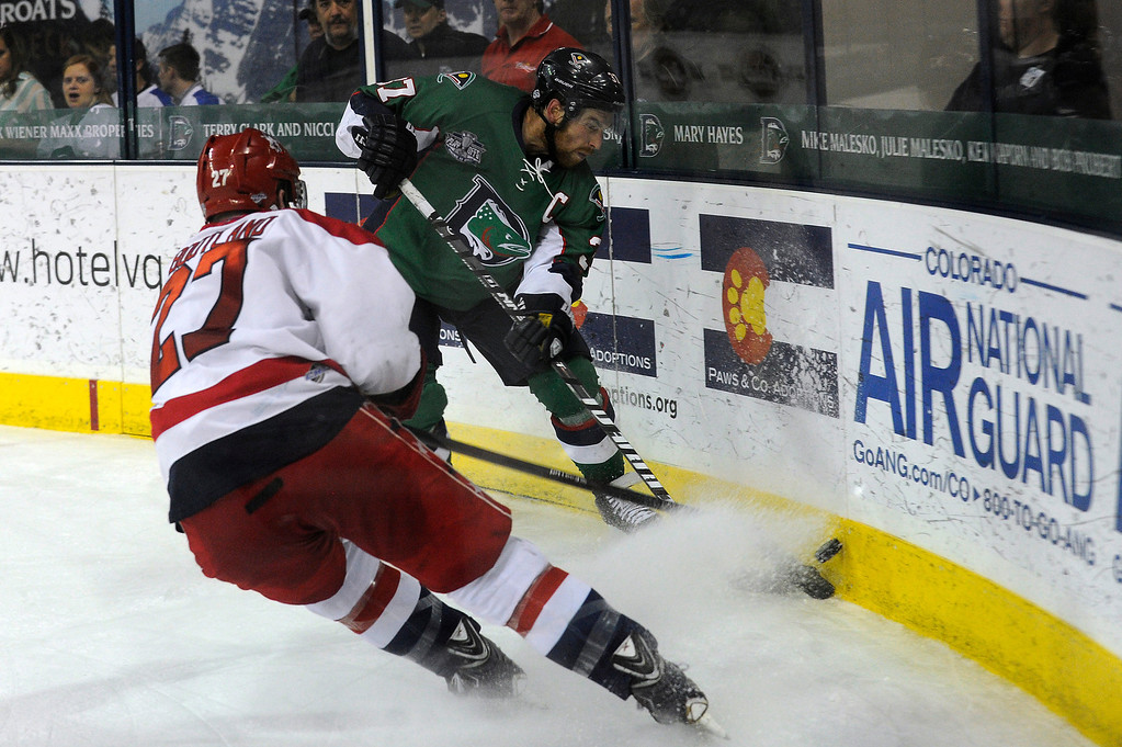 . DENVER, CO - MAY 2: Aaron MacKenzie (37) of the Denver Cutthroats clears the puck off the boards as Darryl Bootland (27) of the Allen Americans attempts to block the pass during the third period of game 1 of the Ray Miron Presidents Cup Finals at the Denver Coliseum in Denver, Colorado on May 2, 2014. (Photo by Seth McConnell/The Denver Post)