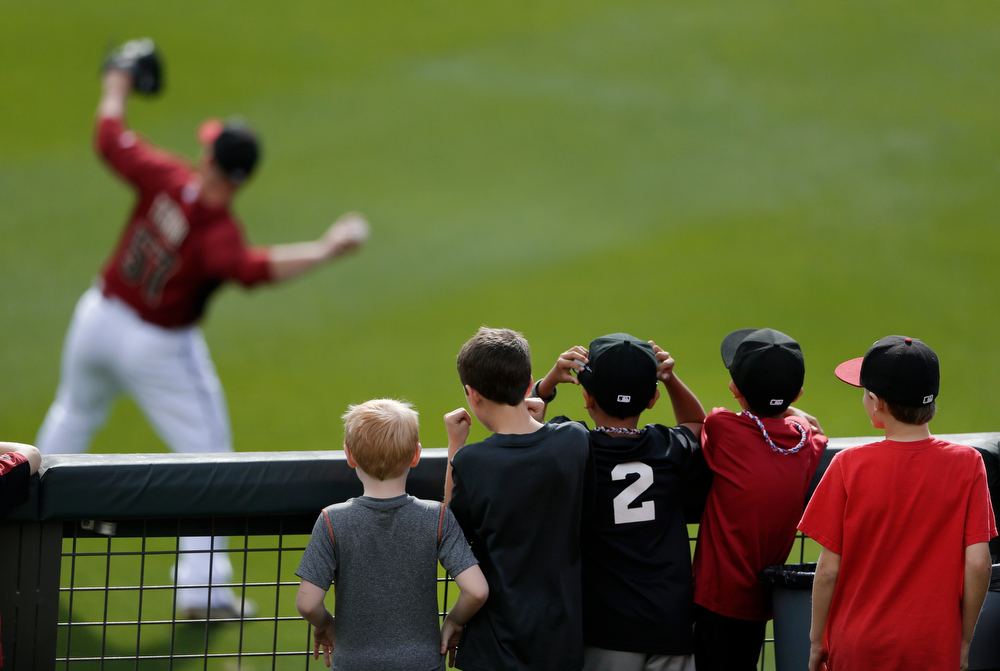 . A group of boys watches from the outfield as Arizona Diamondbacks pitcher Jess Todd warms up between innings during a spring training baseball game between the Diamondbacks and the Colorado Rockies on Friday, Feb. 28, 2014, in Scottsdale, Ariz. (AP Photo/Gregory Bull)