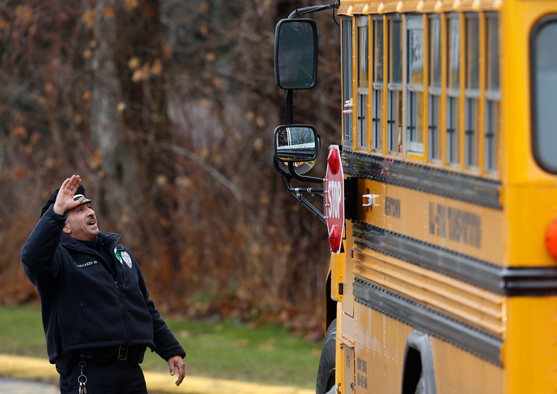 . Easton police officer J. Sollazzo waves to returning children as their bus pulls into Hawley School, Tuesday, Dec. 18, 2012, in Newtown, Conn.  Classes resume Tuesday for Newtown schools except those at Sandy Hook. Buses ferrying students to schools were festooned with large green and white ribbons on the front grills, the colors of Sandy Hook. At Newtown High School, students in sweatshirts and jackets, many wearing headphones, betrayed mixed emotions.  Adam Lanza walked into Sandy Hook Elementary School in Newtown,  Friday and opened fire, killing 26 people, including 20 children, before killing himself.(AP Photo/Jason DeCrow)