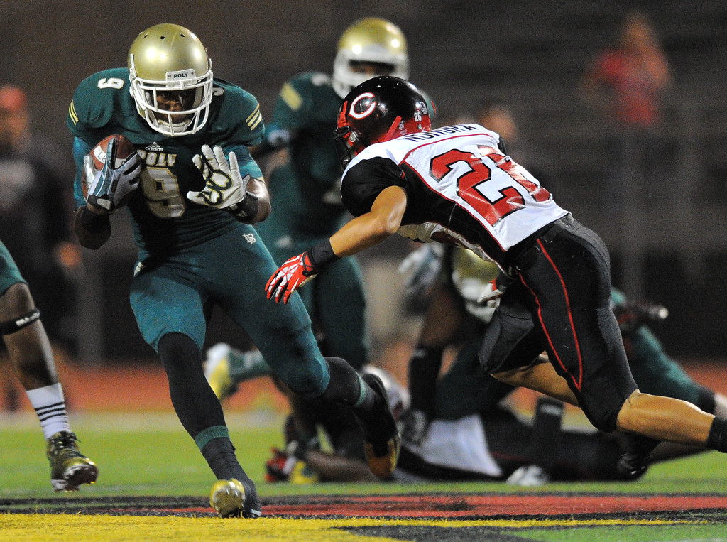 . Long Beach Poly football takes on Centennial (Corona) as part of the Mission Viejo Classic in Mission Viejo, CA on Friday, September 13, 2013. Poly\'s John Smith pushes aside Centennial\'s Manu Nomura on his way to a short gain. (Photo by Scott Varley, Press-Telegram)