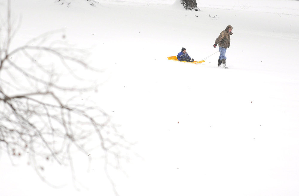 . Tracey Ferguson pulls his son Colten Ferguson, 5, on a sled as they pack down the fresh snow before sliding down the hillside at Riverside Park in Murphysboro, Ill. Wednesday, Dec. 26, 2012. (AP Photo/The Southern Illinoisan, Aaron Eisenhauer)
