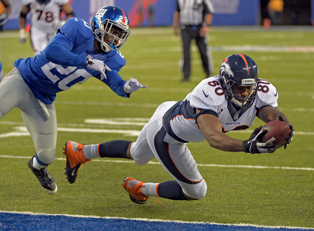 . New York Giants cornerback Prince Amukamara (20) can\'t make the tackle as Denver Broncos tight end Julius Thomas (80) dives over the goal line for a touchdown during the fourth quarter September 15, 2013 MetLife Stadium. (Photo by John Leyba/The Denver Post)