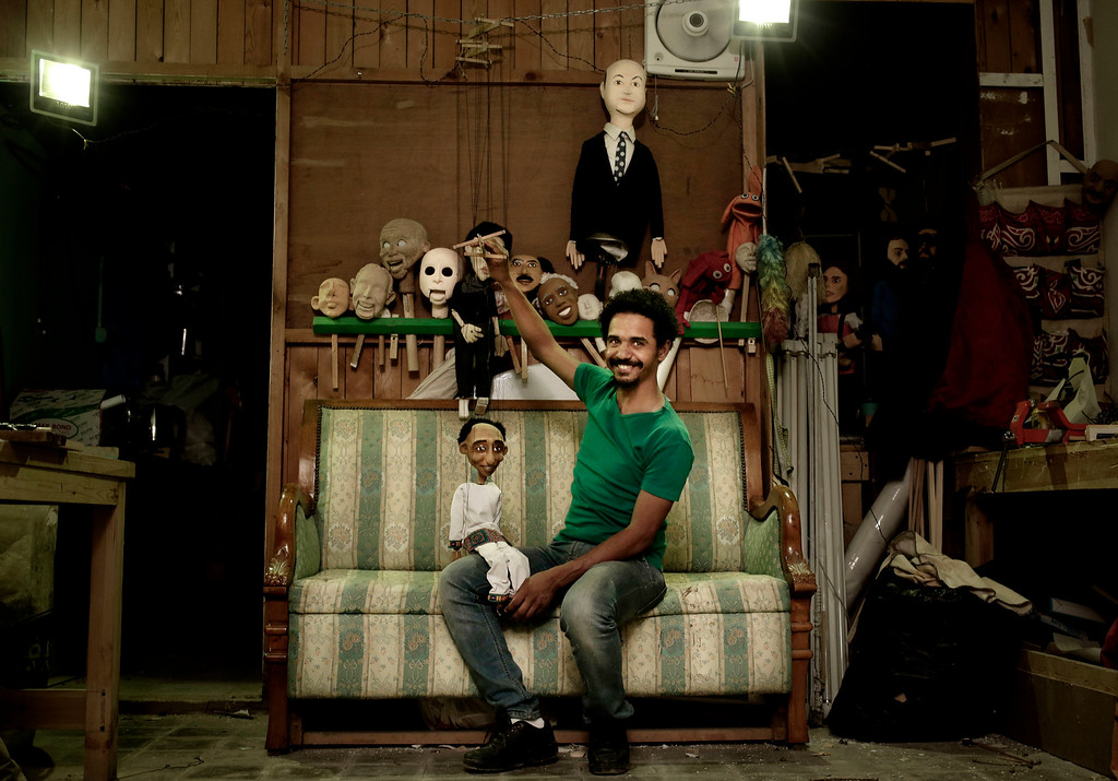 . In this April 24, 2018 photo, Egyptian artist Mohamed Fawzi Bakkar poses for a photograph with his favorite puppets at his workshop, in Cairo, Egypt. Bakkar designs and builds marionettes from scratch, hoping to revive a traditional art. The 32-year-old spends hours or even days designing puppets inspired by Egyptian life -- farmers, street vendors, butchers and the occasional celebrity.  (AP Photo/Nariman El-Mofty)
