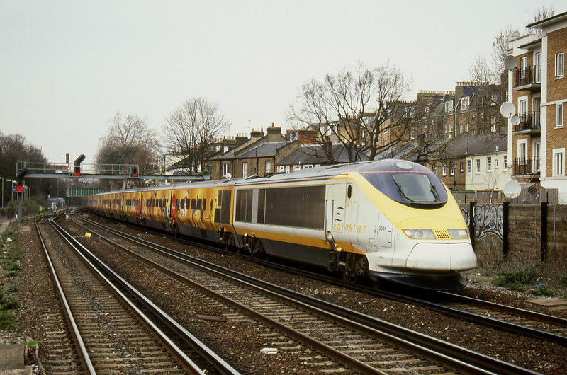 """-- 2004 -- An empty stock working from Eurostar's North Pole Depot in West London to the Eurostar Terminal at London Waterloo heads south through Kensington Olympia led by Class 373 power-car #3001, with the stock in """"Disneyland Resort"""" livery."""