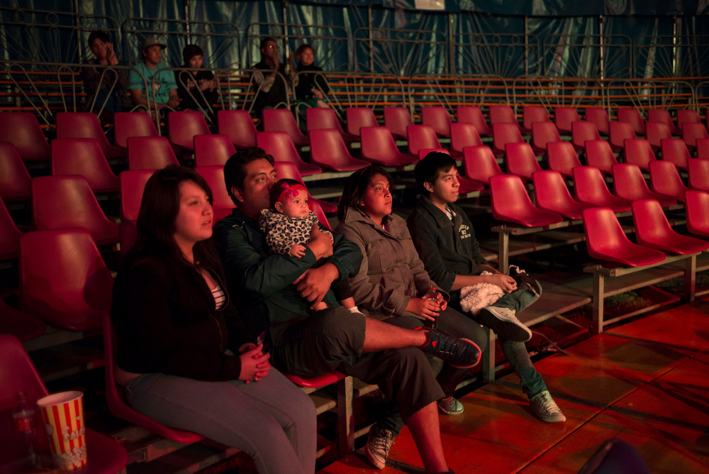 """Description of . In this June 22, 2014, photo a family watches a performance of the Fuentes Gasca Brothers Circus in Mexico City. Attendance has been dwindling at the performances after a six-month ad campaign financed by animal rights groups, said Xochitl Fuentes, one of the owners of the troupe. Now, after the recent legislation which bans the use of animals in the circus, Fuentes fears nobody will want to come. """"If they take the animals out of the circus the circus is going to die,"""" said Fuentes, who is mother to four of the brothers who perform in the circus. (AP Photo/Sean Havey)"""