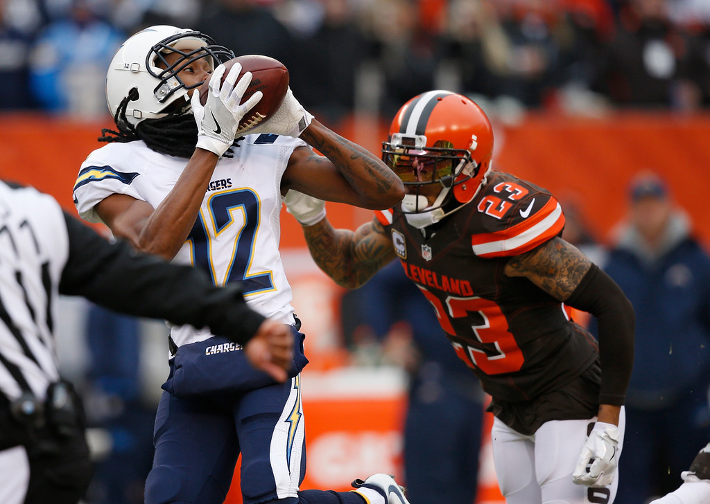 . San Diego Chargers wide receiver Travis Benjamin (12) catches a pass under pressure from Cleveland Browns cornerback Joe Haden (23) in the first half of an NFL football game, Saturday, Dec. 24, 2016, in Cleveland. (AP Photo/Ron Schwane)