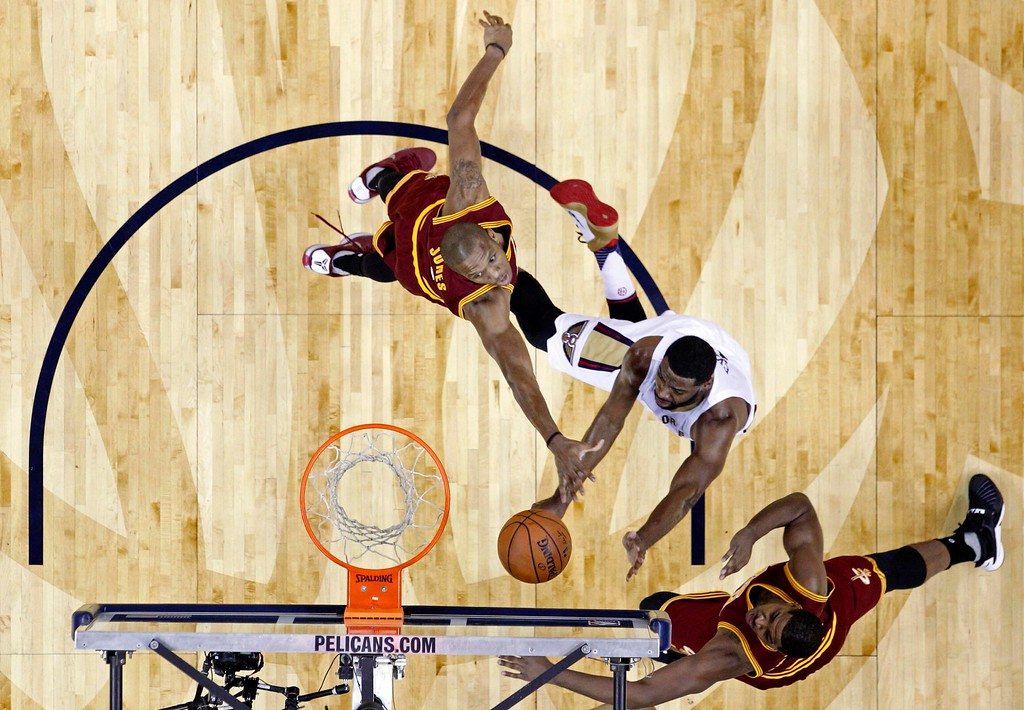 . New Orleans Pelicans guard Tyreke Evans, center, goes to the basket between Cleveland Cavaliers guard James Jones, left, and center Tristan Thompson, right, in the first half of an NBA basketball game in New Orleans, Friday, Dec. 4, 2015. (AP Photo/Gerald Herbert)