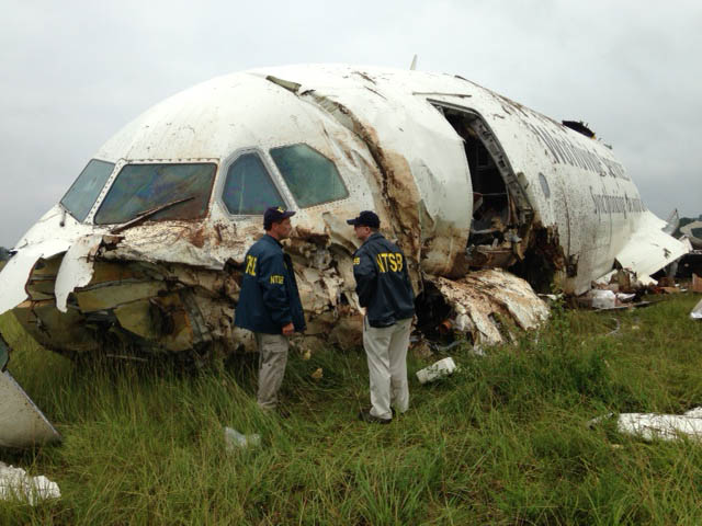 . In this handout photo provided by the National Transportation Safety Board (NTSB), NTSB workers inspect the wreckage of a UPS cargo plane that crashed in a field outside of Birmingham-Shuttlesworth International Airport August 14, 2013 in Birmingham, Alabama.  (Photo by NTSB via Getty Images)