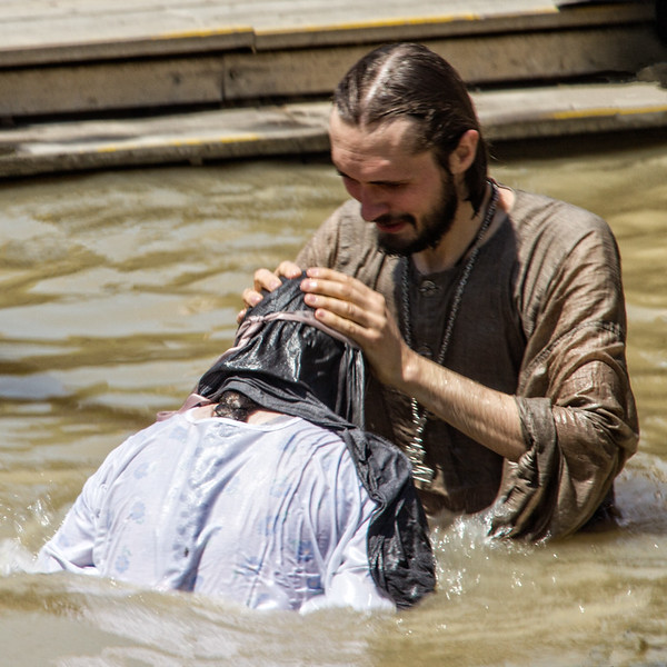 Christian visitor is baptized in the River Jordan.