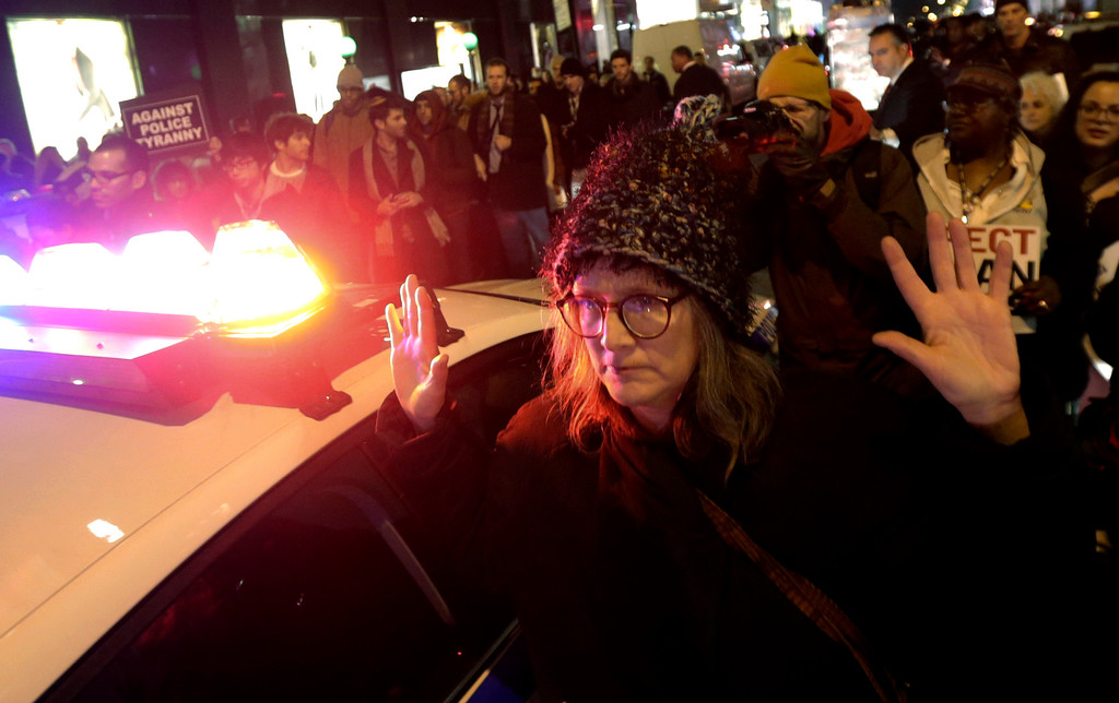 . A woman holds her hands up as she marches near a police vehicle during a protest after it was announced that the New York City police officer involved in the death of Eric Garner is not being indicted, Wednesday, Dec. 3, 2014, in New York. A grand jury cleared the white New York City police officer Wednesday in the videotaped chokehold death of Garner, an unarmed black man, who had been stopped on suspicion of selling loose, untaxed cigarettes, a lawyer for the victim\'s family said. A video shot by an onlooker and widely viewed on the Internet showed the 43-year-old Garner telling a group of police officers to leave him alone as they tried to arrest him. The city medical examiner ruled Garner\'s death a homicide and found that a chokehold contributed to it. (AP Photo/Julio Cortez)