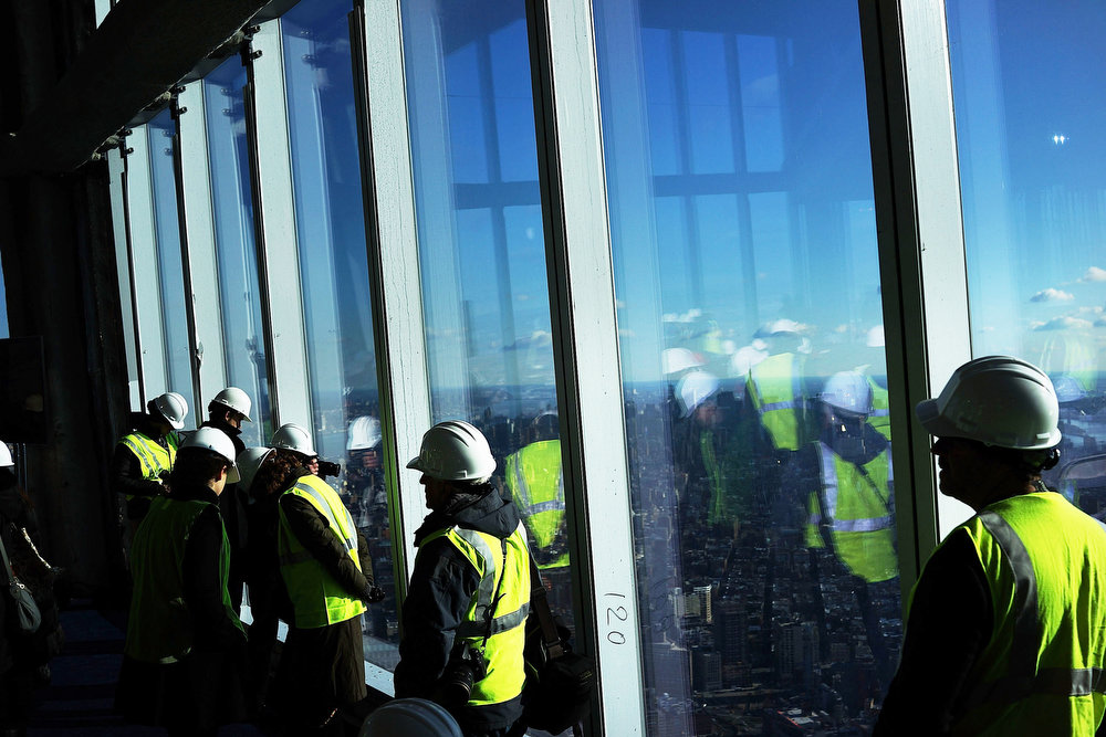 Description of . Visitors stand near the windows of the One World Observatory from the 100th floor of One World Trade Center at the Ground Zero site on April 2, 2013 in New York City. One World Observatory, which is situated more than 1,250 feet over lower Manhattan, will open to the public in 2015 and will include a pre-show theater, multiple spaces that allow for panoramas of the New York City region and numerous dining options. When completed, One World Trade Center will be the tallest building in the Western Hemisphere at 1776 feet.  (Photo by Spencer Platt/Getty Images)