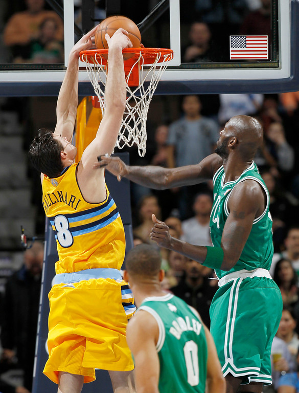 . Denver Nuggets forward Danilo Gallinari, of Italy, drops the ball in for a basket as Boston Celtics forward Kevin Garnet, right, and guard Avery Bradley watch during the first quarter of an NBA basketball game in Denver on Tuesday, Feb. 19, 2013. (AP Photo/David Zalubowski)