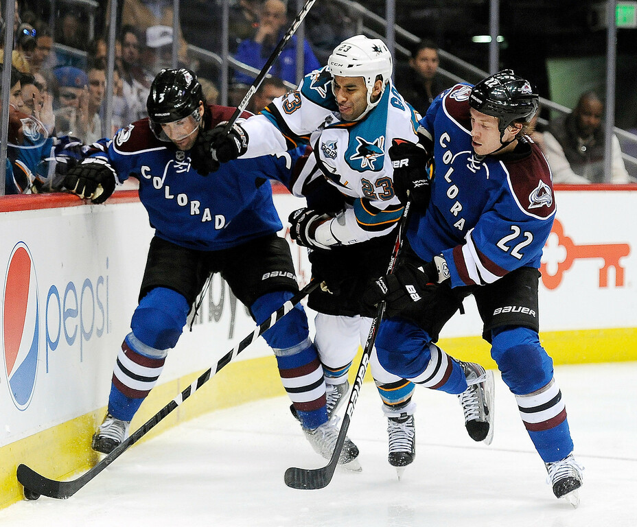 . Colorado Avalanche defenseman Ryan O\'Byrne, left, and defenseman Matt Hunwick, right, battle for control of the puck with San Jose Sharks center Scott Gomez, center, in the second period of an NHL hockey game on Sunday, March 10, 2013, in Denver.  (AP Photo/Chris Schneider)
