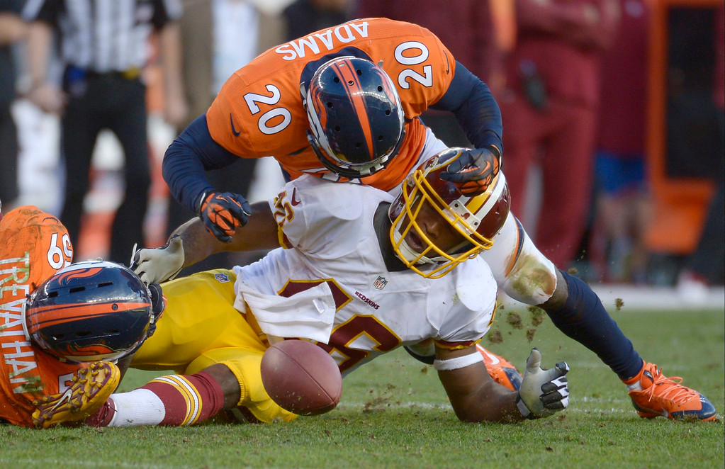 . Denver Broncos outside linebacker Danny Trevathan (59) and Denver Broncos strong safety Mike Adams (20) cause a fumble by Washington Redskins running back Alfred Morris (46) during the fourth quarter at Sports Authority Field at Mile High in Denver on October 27, 2013. (Photo by Tim Rasmussen/The Denver Post)
