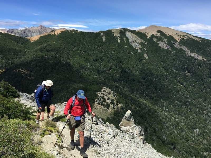 Two hikers on a trail surrounded by the mountains of northern Patagonia.