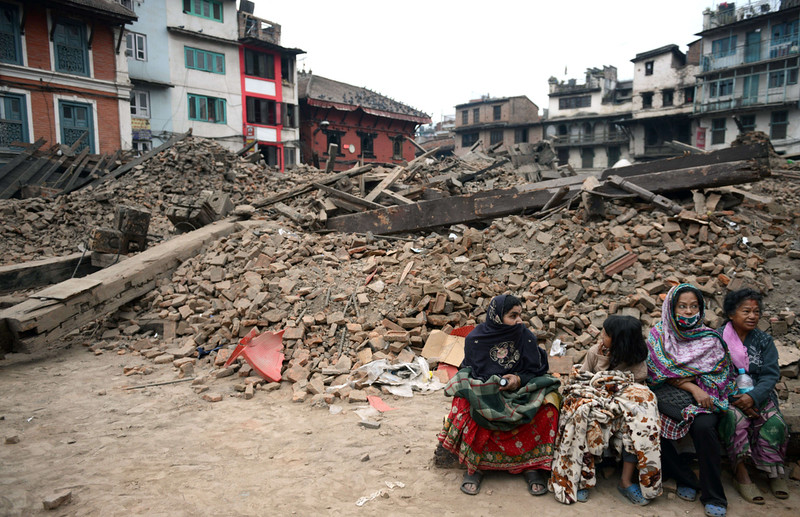 . Nepalese residents sit near buildings severely damaged by an earthquake in Kathmandu on April 26, 2015.  Rescuers in Nepal are searching frantically for survivors of a quake that killed more than 2,000, digging through rubble in the devastated capital Kathmandu and airlifting victims of an avalanche at Everest base camp. PRAKASH MATHEMA/AFP/Getty Images