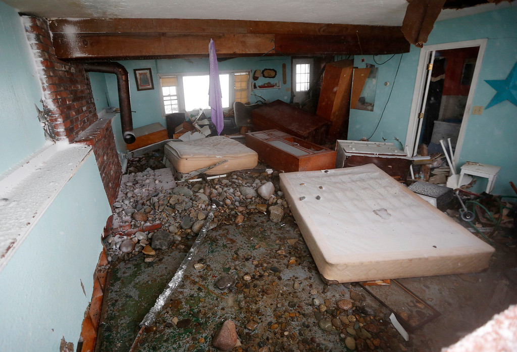 . Rocks and debris litter the floor of a house damaged by ocean waves during a winter storm in Marshfield, Mass., Tuesday, Jan. 27, 2015. The storm punched out a section of the seawall in the coastal town of Marshfield, police said.(AP Photo/Michael Dwyer)