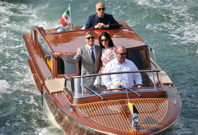 . George Clooney waves as he cruises the Grand Canal on a boat with his wife Amal Alamuddin, after leaving the Aman luxury Hotel in Venice, Italy, Sunday, Sept. 28, 2014. George Clooney married human rights lawyer Amal Alamuddin Saturday, the actor\'s representative said, out of sight of pursuing paparazzi and adoring crowds. (AP Photo/Luigi Costantini)