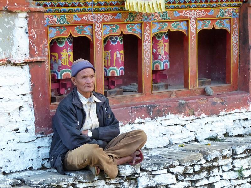 man by prayer wheels in Tawang.jpg
