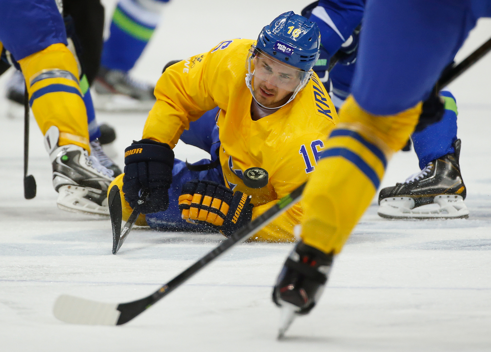 . Sweden forward Marcus Kruger dives after the puck against Slovenia in the third period of a men\'s ice hockey game at the 2014 Winter Olympics, Wednesday, Feb. 19, 2014, in Sochi, Russia. (AP Photo/Julio Cortez)
