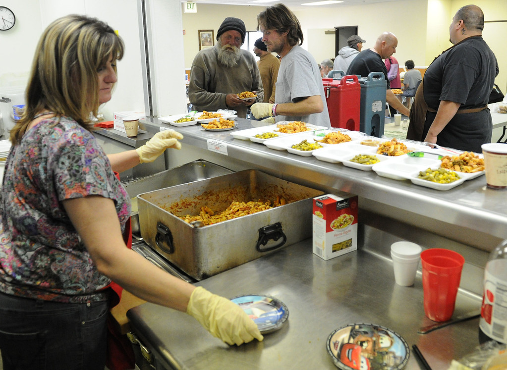 . (John Valenzuela/Staff Photographer)  Volunteer Debbie Godsey, Eric Davis and head cook Armando Campos help serve dinner at the Salvation Army in Redlands, Friday, March 22. 2013.  The Redlands Salvation Army gives out dinner on a daily basis to the hungry, provides shelter to the homeless when it\'s cold, and clean showers to wash up.