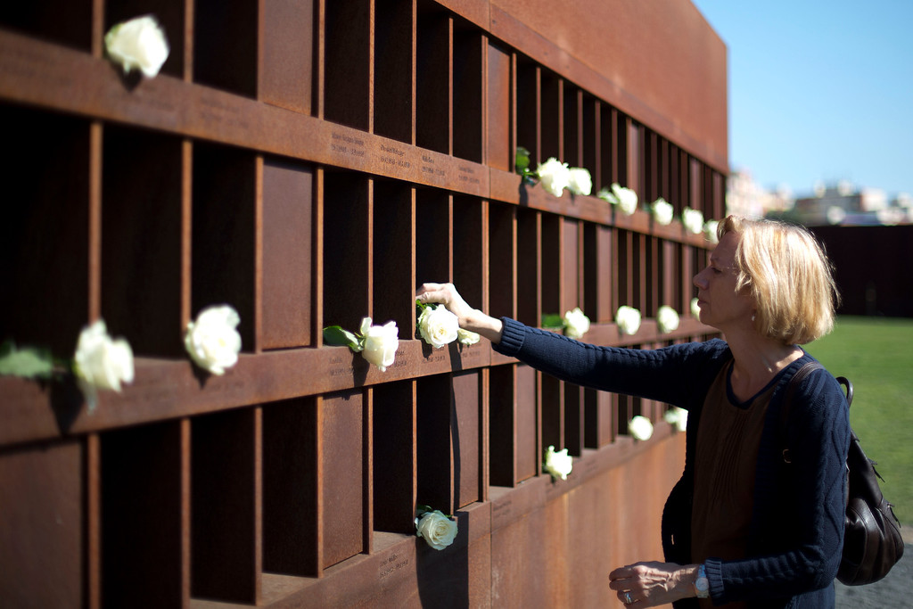 . A woman lays a flower before a wreath laying ceremony at the memorial of the Berlin Wall in the Bernauer Strasse, on August 13, 2012 on the anniversary of the construction of the Berlin Wall.  (Photo credit DAVID GANNON/AFP/GettyImages)
