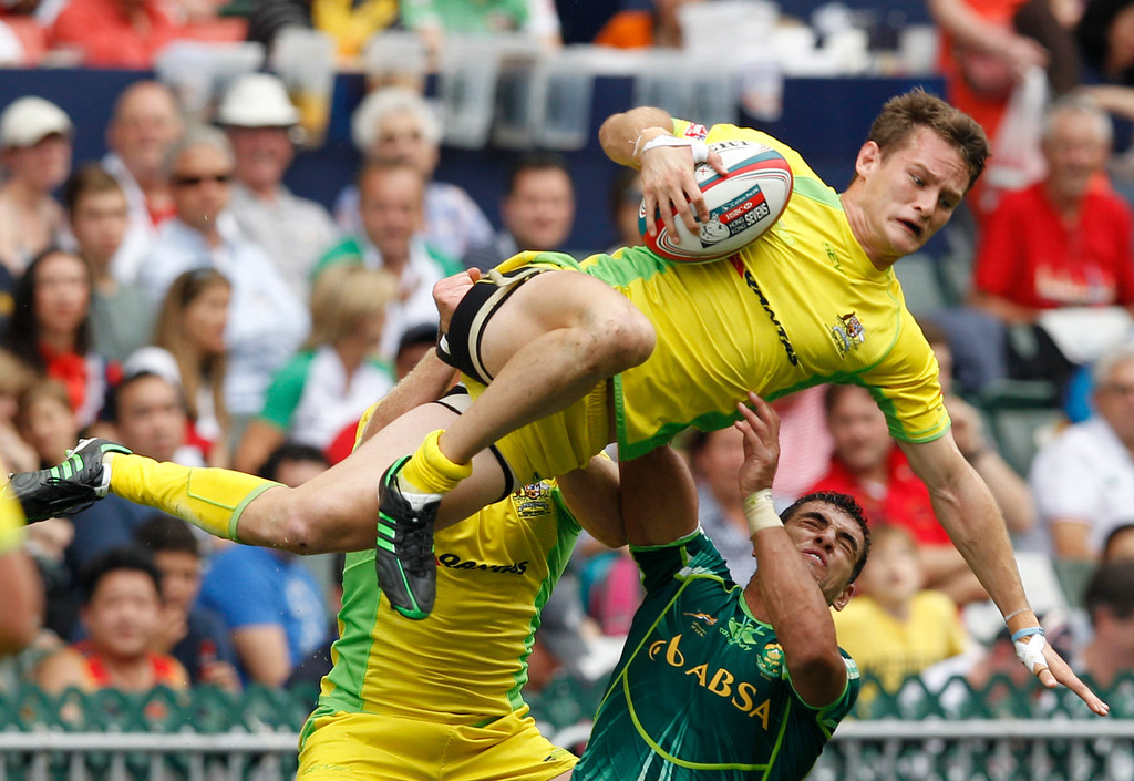 . Con Foley of Australia, center, is tackled by Chris Dry of South Africa, right during their match at the Hong Kong Sevens rugby tournament in Hong Kong Saturday, March 23, 2013. Australia won 21-12. (AP Photo/Kin Cheung, File)