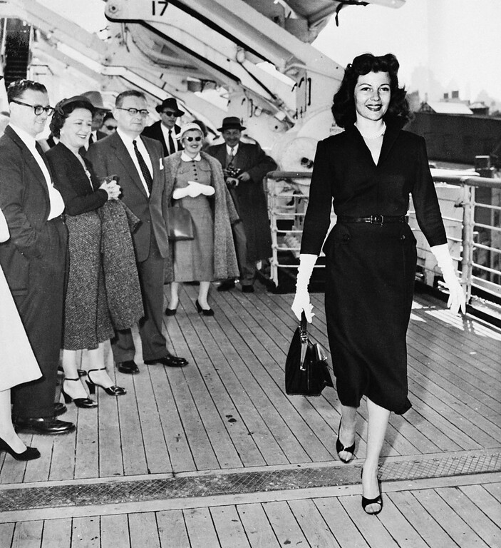 . Shapely Rita Hayworth, who never looked better, walks on the promenade deck of the Queen Elizabeth, much to the delight of her fellow passengers, as the liner docked. The actress is returning to the U.S. to make her first movie in three years. To be released by Columbia, it will be called Fire Down Below. (Copyright Bettmann/Corbis / AP Images)