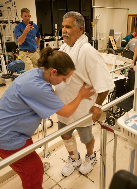 ". Richard Torres of Livingston tries to see if he has made any improvement after using ""Ekso\"" a robotic exoskeleton device at the Rehabilitation Center at Santa Clara Valley Medical Center in San Jose Wednesday, July 17, 2013. He is helped by VMH physical therapist Tawni Ybarra as Ekso Bionics physical therapist Darrell Musick looks on.  (Patrick Tehan/Staff)"