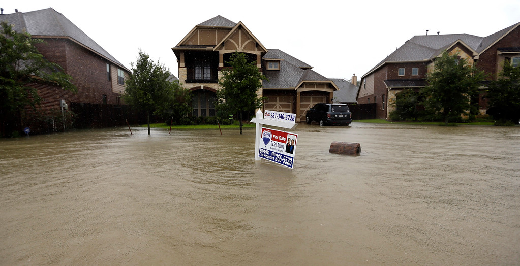 . A for sale signs stands in front of a home as floodwaters from Tropical Storm Harvey rise Monday, Aug. 28, 2017, in Spring, Texas. (AP Photo/David J. Phillip)