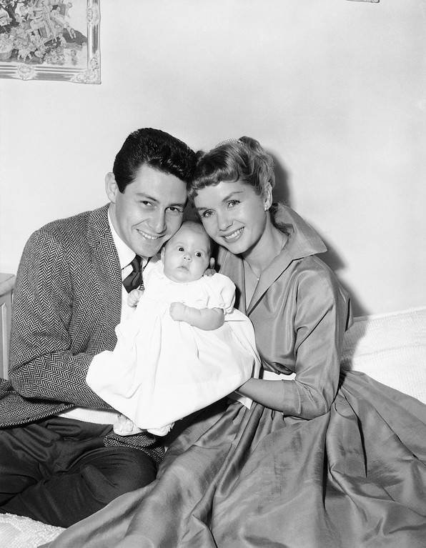 """. Eddie Fisher and Debbie Reynolds appear before the camera in their real roles of happy parents as they and their young daughter, Carrie Frances Fisher, pose for their first family group picture, in Hollywood, Jan. 2, 1957.   Carrie Frances was born Oct.21, 1956.    The young stars, appropriately, are appearing in a film titled \""""Bundle of Joy.\"""" (AP Photo)"""