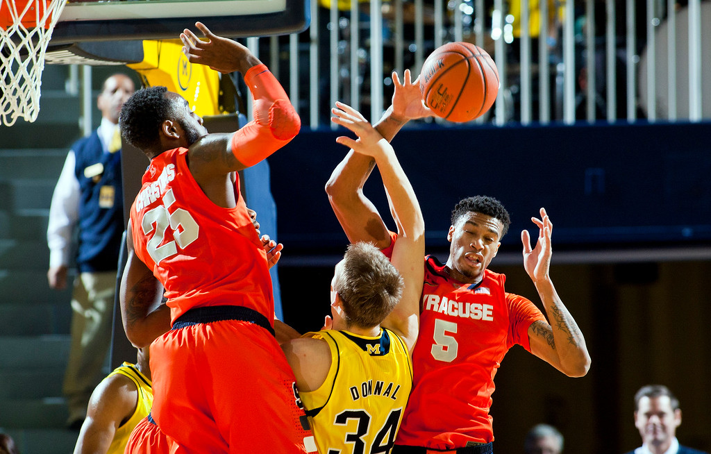 . Syracuse forward Rakeem Christmas (25) and forward Chris McCullough (5) contest for a rebound with Michigan forward Mark Donnal (34), in the first half of an NCAA college basketball game at Crisler Center in Ann Arbor, Mich., Tuesday, Dec. 2, 2014. (AP Photo/Tony Ding)