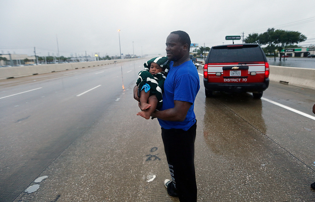 . Alvin Whitfield holds his eight-month-old sone Alvin Whitfield, Jr. as he waits for a ride after being rescued by members of the Louisiana Department of Wildlife and Fisheries and the Houston Fire Department during Tropical Storm Harvey in Houston, Monday, Aug. 28, 2017. (AP Photo/Gerald Herbert)
