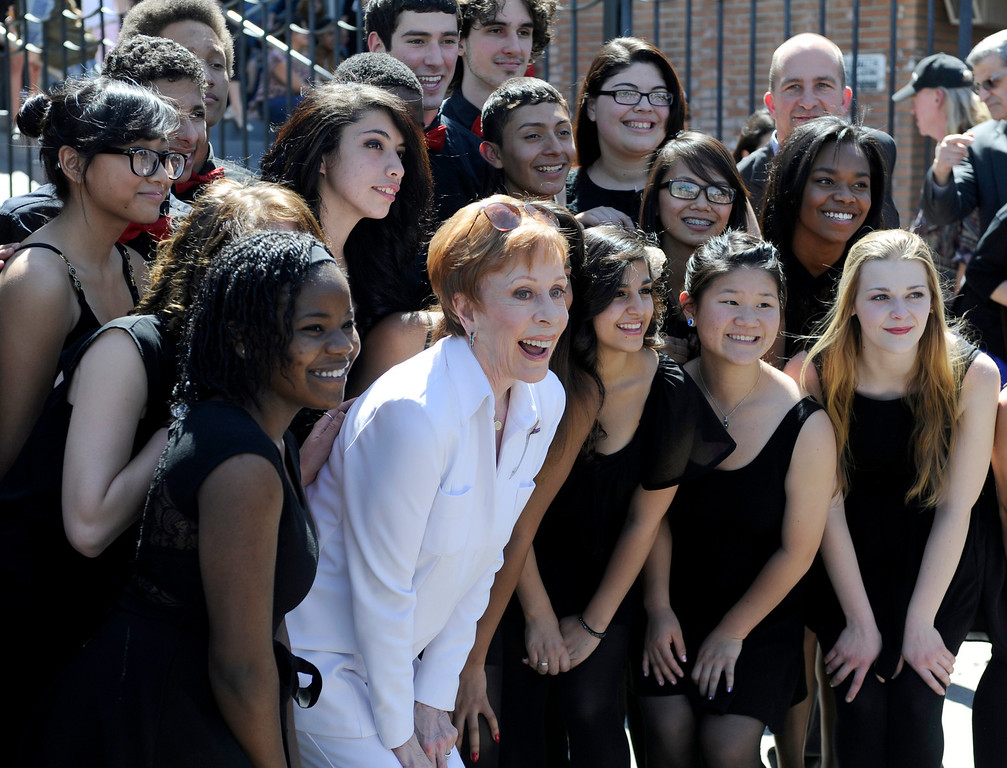""". Carol Burnett poses for photos with the Hollywood High School choir H2O. Burnett, award-winning actress, comedienne and best-selling author, was honored by the City of Los Angeles for her lifetime achievements with the naming of Carol Burnett Square at the intersection of Highland Avenue and Selma Avenue. The Square is adjacent to Hollywood High School where Burnett attended. Students from the school choir, \""""H2O\"""" sang �I�m so glad we had this time together,� before Burnett and LA City Councilman Tom LaBonge unveiled her street sign. Hollywood, CA 4/18/2013(John McCoy/Staff Photographer"""