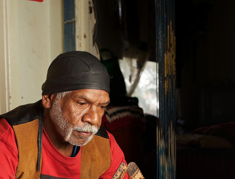 Contemplative Aboriginal Elder of the Wurundjeri People, indoors and on a blurred background