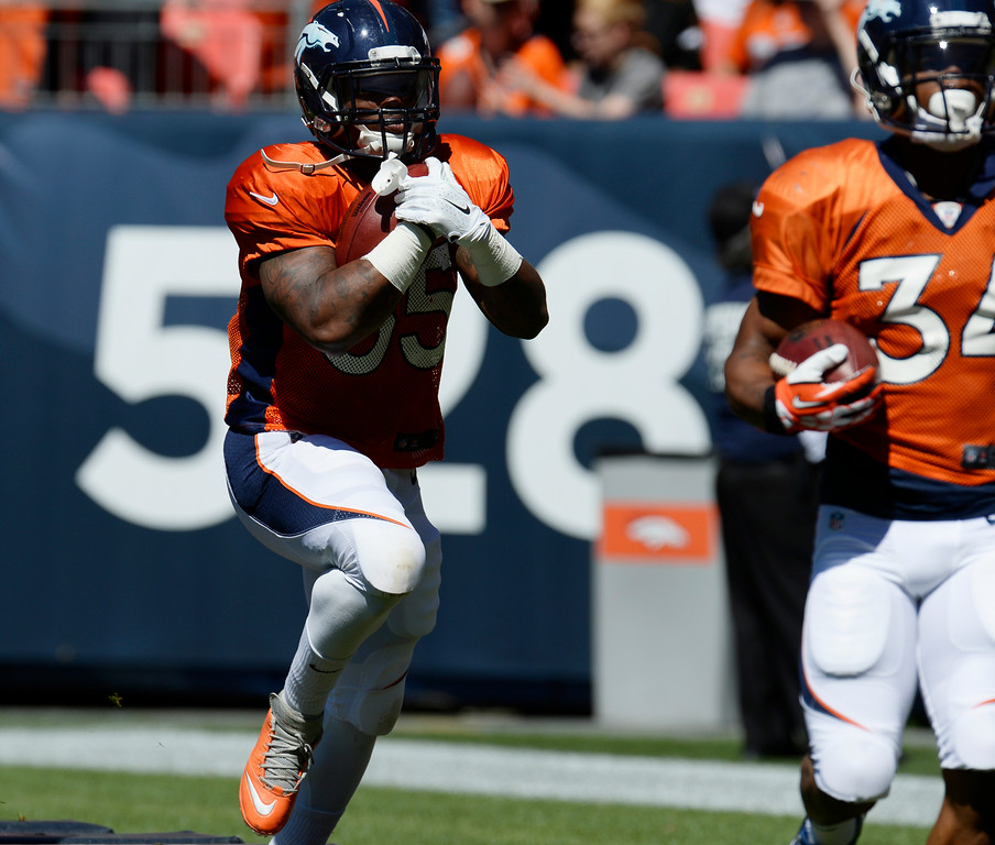 . Denver Broncos RB, Kapri Bibbs, left, during practice at Sports Authority Field at Mile High Saturday afternoon, August 02, 2014. (Photo By Andy Cross / The Denver Post)