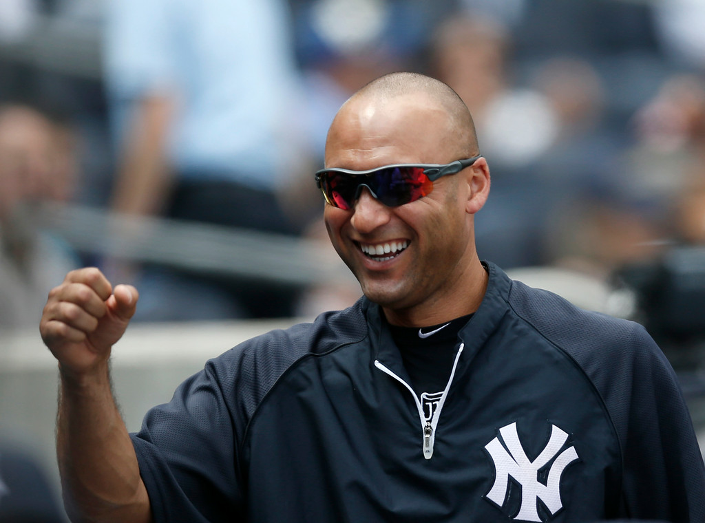 . New York Yankees Derek Jeter, sitting out a game, greets teammates in the dugout during a baseball game at Yankee Stadium in New York, Thursday, Aug. 7, 2014.  (AP Photo/Kathy Willens)