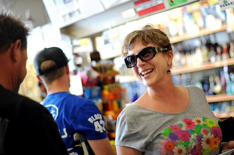 """. Susan McColly is all smiles as she purchases Powerball tickets at Alcon Liquor in Canoga Park, CA Friday.  The liquor store is listed as a \""""Lucky Retailer\"""" on the California Lottery website.  By Friday at noon the Powerball jackpot had grown to an estimated 00 million, the largest amount in the game\'s history.(Andy Holzman/Staff Photographer)"""