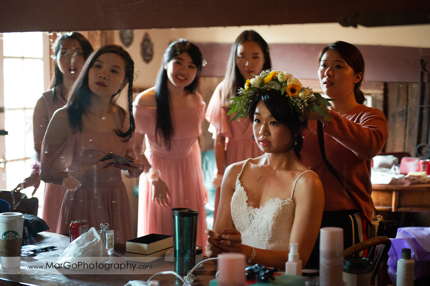 bride in white wedding dress sitting in front of mirror with yellow flower cronw at Long Branch Saloon & Farms in Half Moon Bay