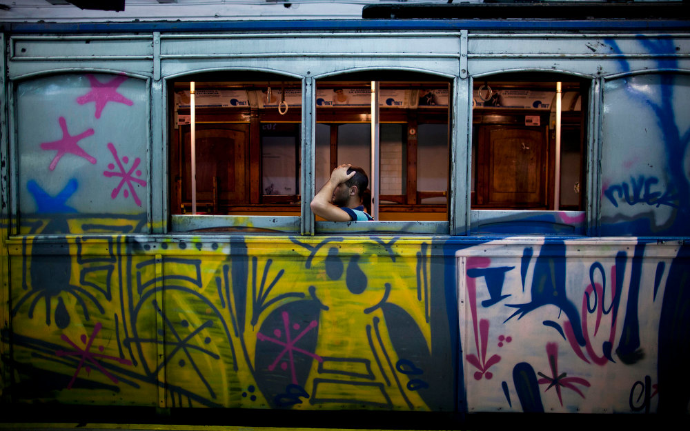 ". A passenger travels in a wooden carriage car on Line A of the historic subway in Buenos Aires, Argentina, Friday, Jan. 11, 2013.  The almost 100-year-old ""La Brugeoise\"" wooden carriages will stop working today and be replaced soon by modern Chinese units. The 90 Belgian cars began rolling in 1913 on Latin America\'s first subway line and are the oldest subway cars still operating in the world, carrying 160,000 passengers on the line daily. (AP Photo/Natacha Pisarenko)"
